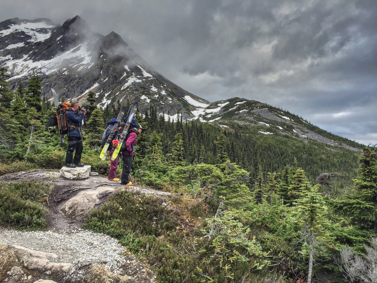 Two hikers loaded with backpacks and skis survey a mountain view from a rocky outcrop