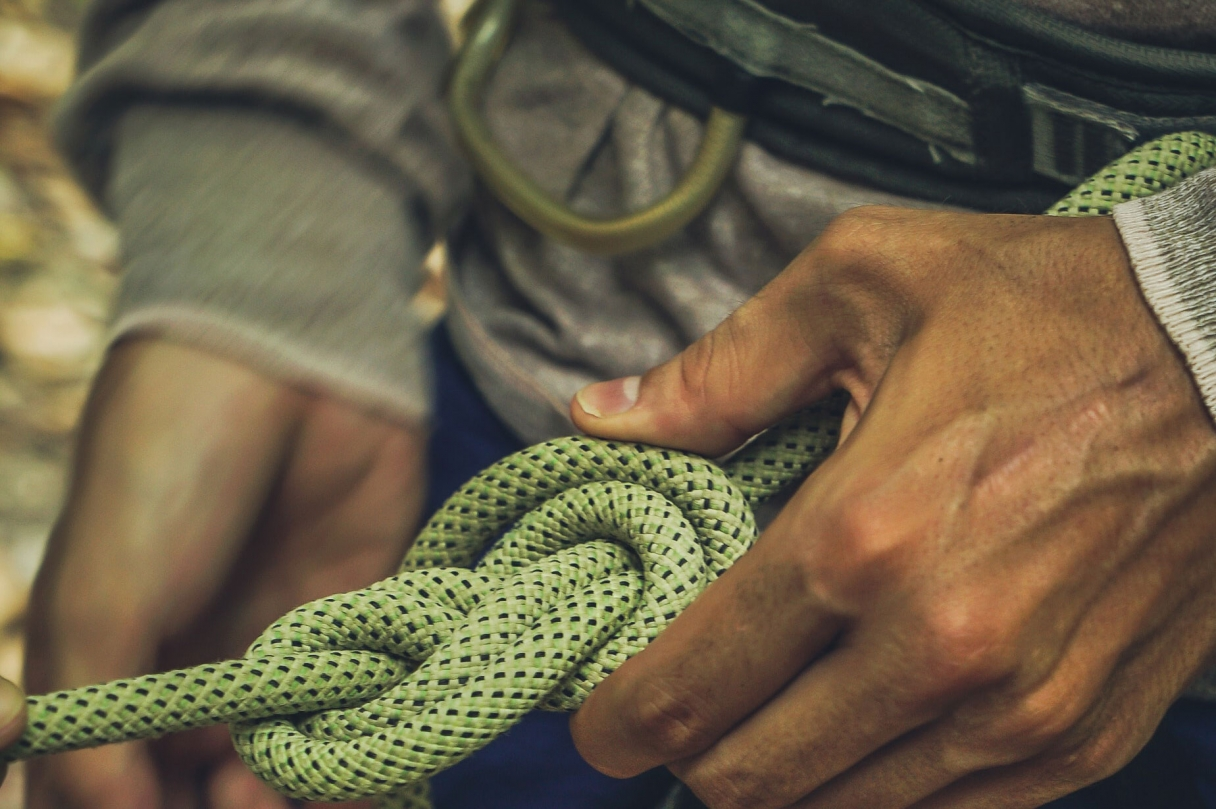 A climber's hands secure a safety knot